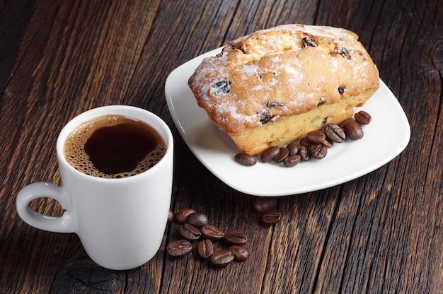 Café preto e bolinho com passas na mesa de madeira escura