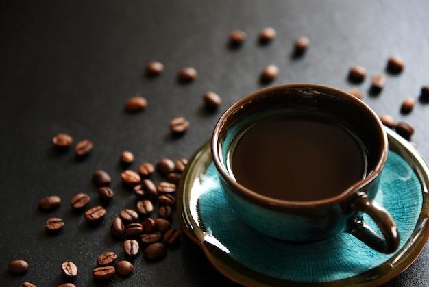 Café preto e café em grão na mesa preta