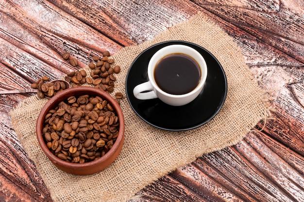 Café preto e grãos de café na vista superior de superfície de madeira de saco de carvão