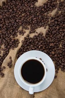 Café preto e grãos de café no saco