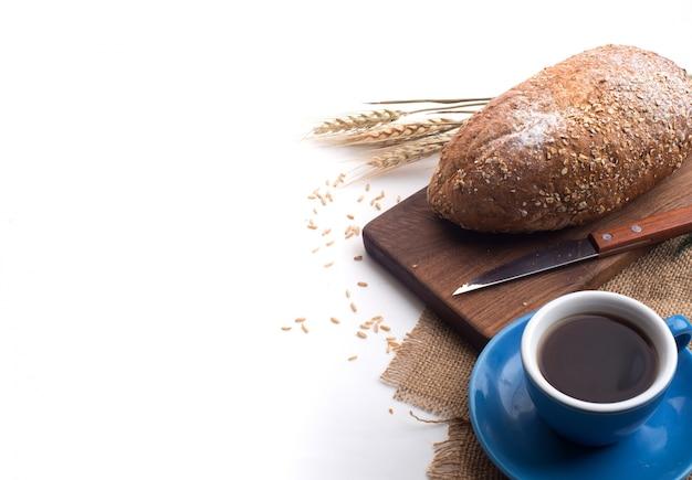 Café preto e pão de trigo integral para o café da manhã no fundo branco