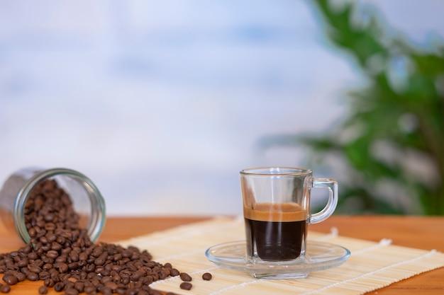Café preto em copo de vidro e grãos de café na mesa de madeira
