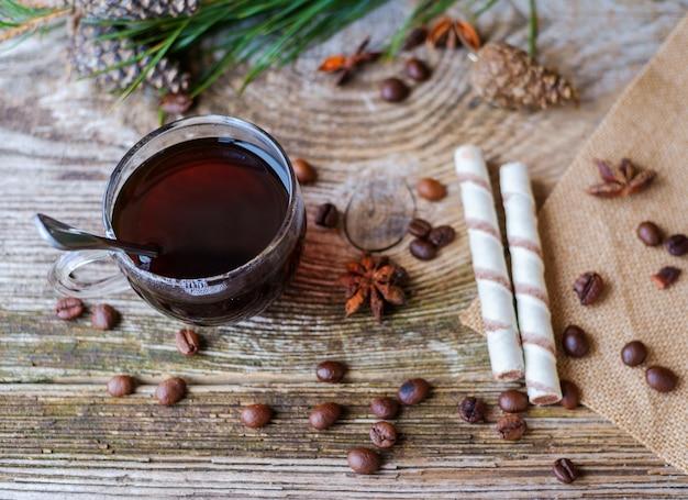 Café preto em copo de vidro na mesa de madeira com galhos de pinheiro, grãos de café, estrelas de anis, canela e rolos de wafer
