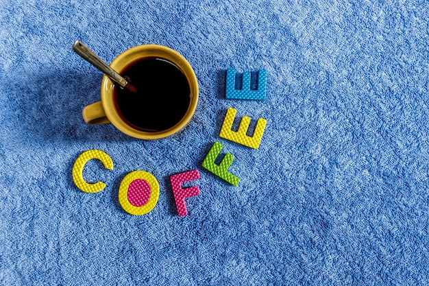 Café preto em um copo com fundo de pano azul e um material de cortiça onde se lê café