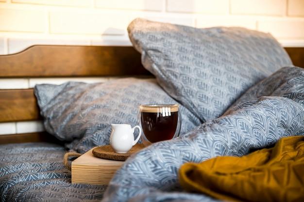 Café preto em um copo transparente na cama de manhã de outono