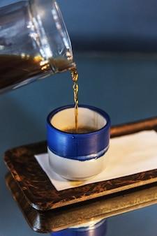 Café preto em um pequeno copo azul