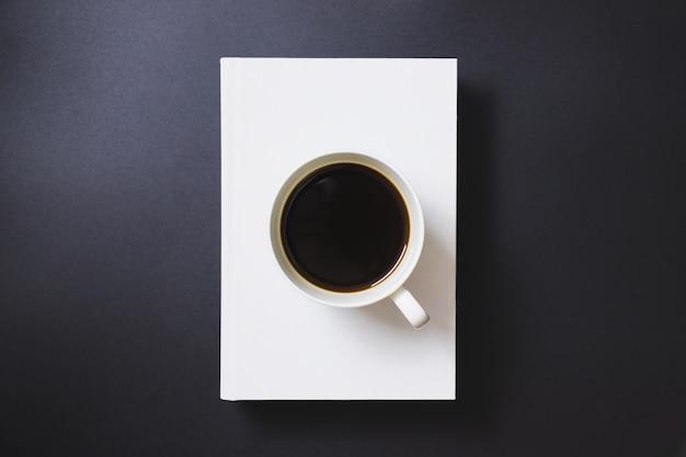 Café preto em uma caneca de café branca, colocada em livros brancos sobre um fundo preto