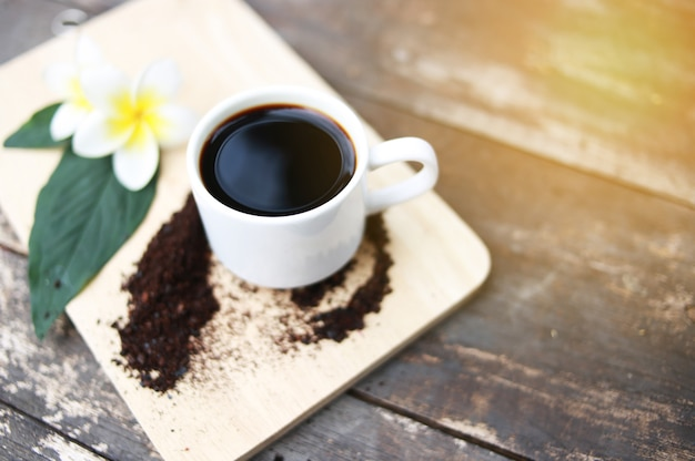 Café preto em uma mesa de madeira com luz solar.