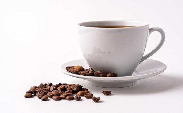 Café preto em uma xícara branca e grãos de café isolados no fundo branco, copie o espaço para o texto.