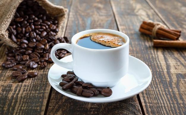 Café preto em uma xícara branca, grãos de café, paus de canela em um fundo de madeira velho.