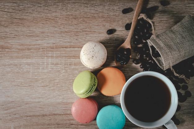 Café preto em uma xícara com grãos de café e biscoitos no fundo da mesa de madeira