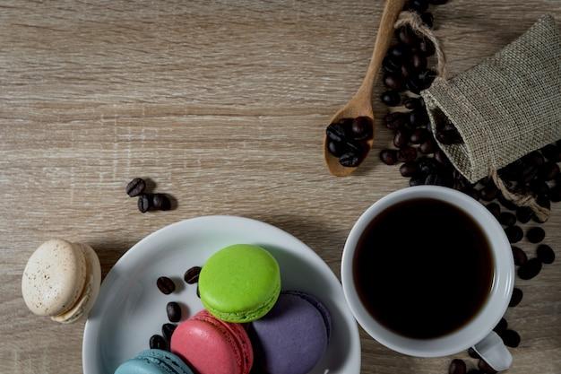 Café preto em uma xícara com grãos de café e macarons no fundo da mesa de madeira