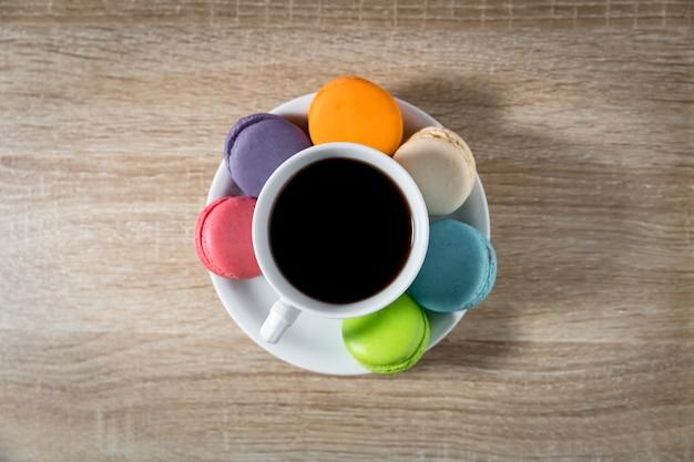 Café preto em uma xícara com macarons no prato branco no fundo da mesa de madeira