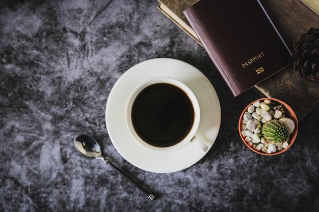 Café preto em uma xícara de café branca e cacto colocado