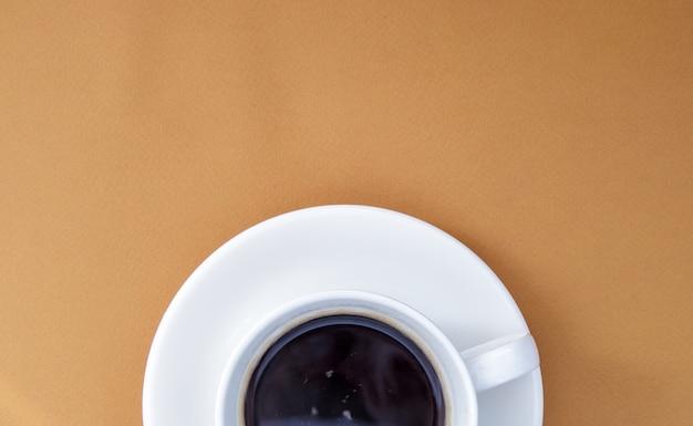 Café preto em uma xícara de café branco sobre um fundo suave. vista superior, configuração plana, copie o espaço. café e bar, conceito de arte barista. café natural ou instantâneo feito na hora em uma xícara. fundo de café.