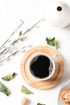 Café preto em uma xícara e folhas em uma mesa branca