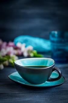Café preto em uma xícara turquesa e flores sobre fundo preto de madeira