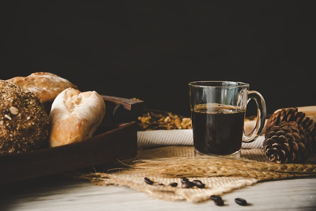 Café preto em vidro é colocado no chão de madeira - conceito ainda vida