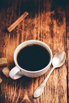 Café preto em xícara branca com açúcar e canela em pau
