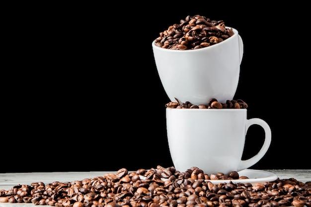 Café preto em xícara branca e grãos de café sobre fundo preto.