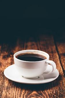 Café preto em xícara branca sobre superfície de madeira