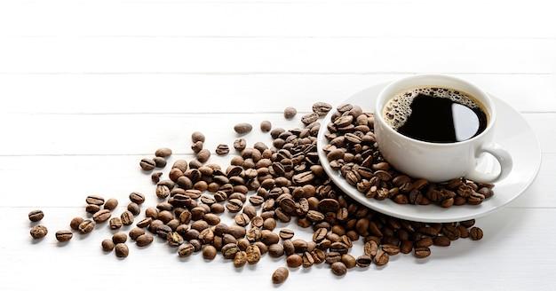 Café preto em xícara de cerâmica branca com grãos de café em uma mesa branca