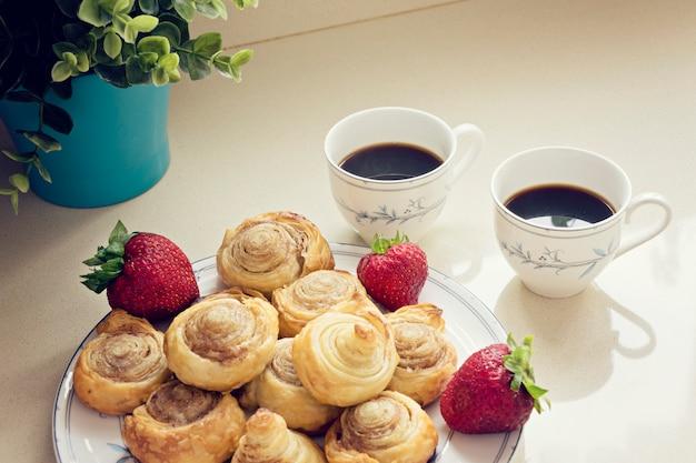Café preto fresco da manhã e pãezinhos acabados de fazer