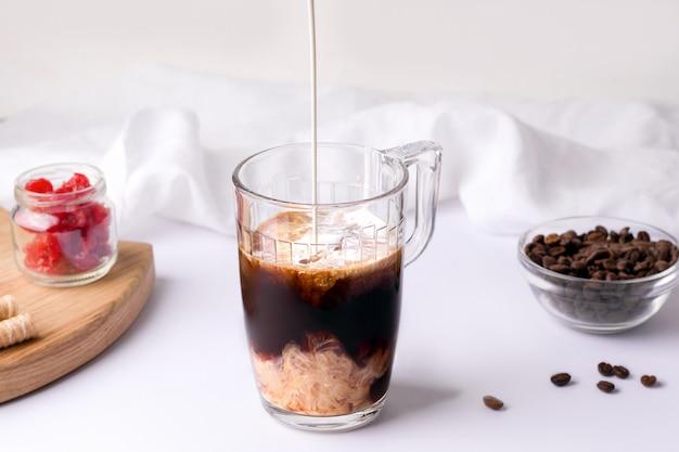 Café preto frio em uma xícara sobre um fundo branco onde o creme é derramado