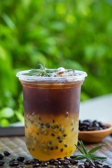 Café preto gelado com maracujá em superfície de madeira