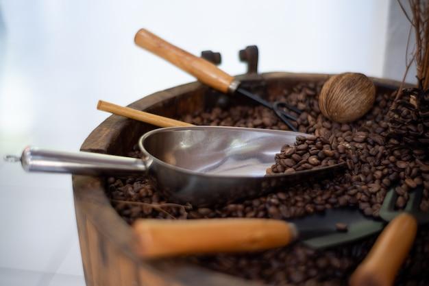 Café preto grãos de café torrados e café em colheres de madeira e paus de canela