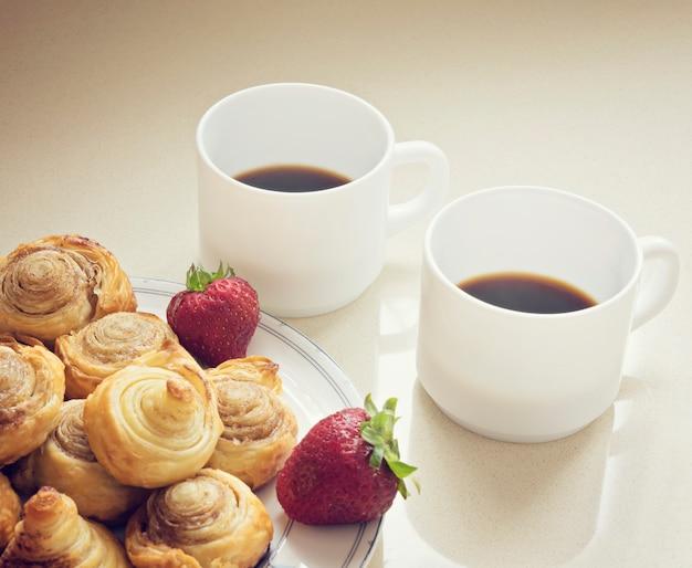 Café preto matinal e pãezinhos acabados de fazer
