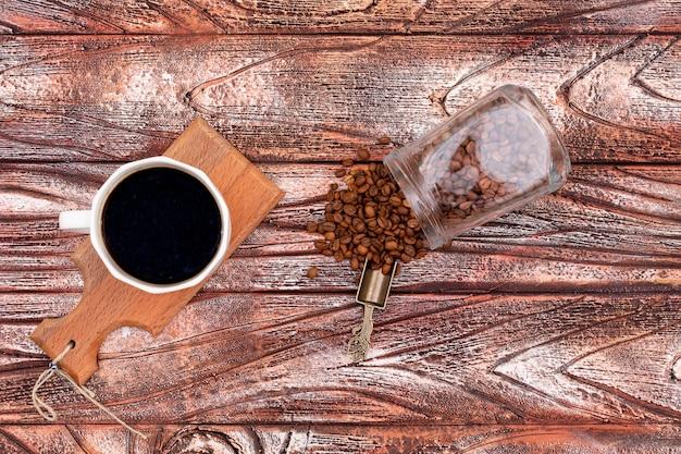 Café preto na placa de madeira com pote de grãos de café vista superior