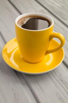 Café preto na xícara amarela na superfície cinza de madeira