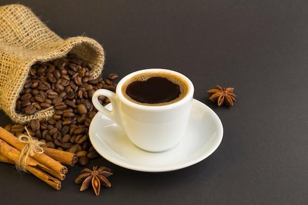 Café preto na xícara branca, canela e grãos de café no fundo escuro