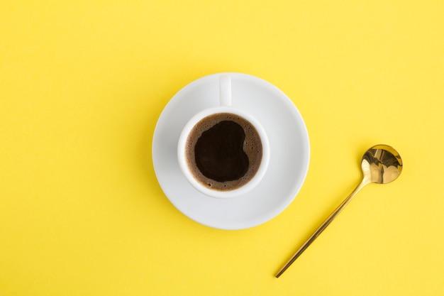 Café preto na xícara branca e colher de ouro no centro da mesa amarela. copie o espaço. vista do topo.