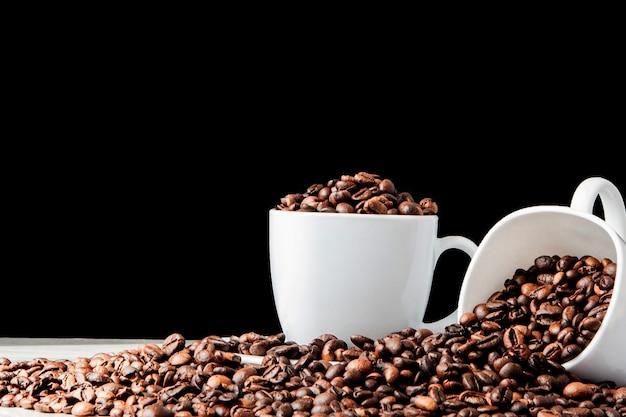 Café preto na xícara branca e grãos de café em fundo preto. vista superior, espaço para texto