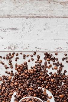 Café preto na xícara branca e grãos de café sobre fundo claro de madeira. vista superior, espaço para texto