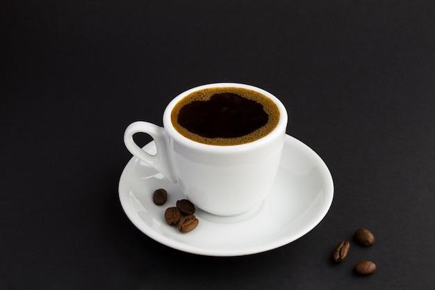 Café preto na xícara branca e grãos de café