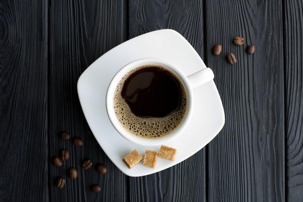 Café preto na xícara branca no centro da mesa de madeira preta. vista do topo. copie o espaço. fechar-se.