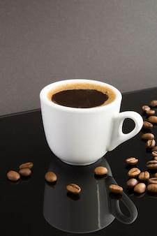 Café preto na xícara branca no fundo escuro