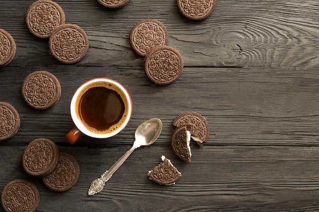 Café preto na xícara de cerâmica marrom e biscoitos de chocolate na madeira preta