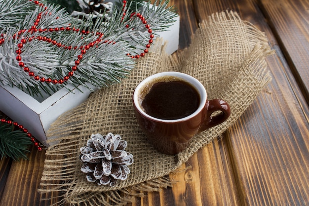 Café preto na xícara de cerâmica marrom e composição de natal
