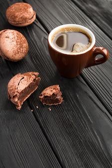 Café preto na xícara de cerâmica marrom e macaroons de chocolate na mesa de madeira preta. copie o espaço.