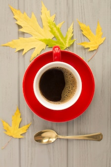 Café preto na xícara de cerâmica vermelha e folhas amarelas na mesa de madeira cinza. vista do topo. composição de outono.