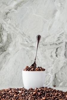Café preto na xícara e grãos de café sobre fundo de mármore.