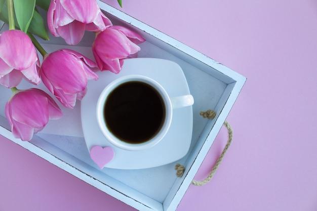 Café preto na xícara e tulipas cor de rosa na bandeja de madeira branca. vista superior.