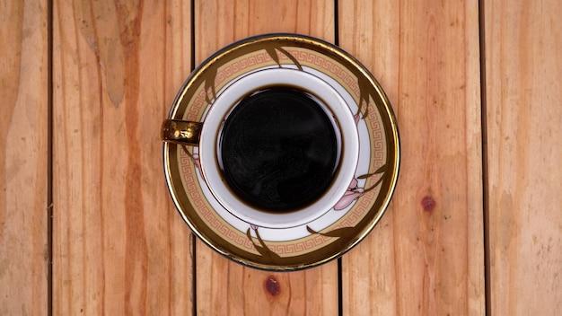 Café preto na xícara em cima da mesa de madeira