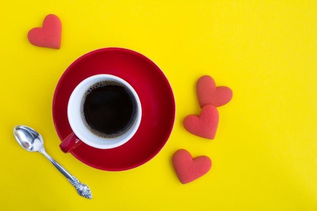 Café preto na xícara vermelha e biscoitos em forma de coração vermelho em amarelo