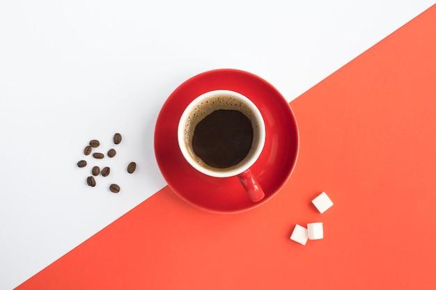 Café preto na xícara vermelha no centro da mesa bicolor. copie o espaço. vista do topo.