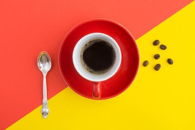Café preto na xícara vermelha no centro da mesa colorida. copie o espaço. vista do topo.